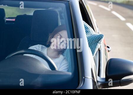 Jeune femme fatiguée conducteur endormi sur l'oreiller sur le volant, se reposant après de longues heures de conduite d'une voiture. Fatigue. Privation de sommeil. Banque D'Images