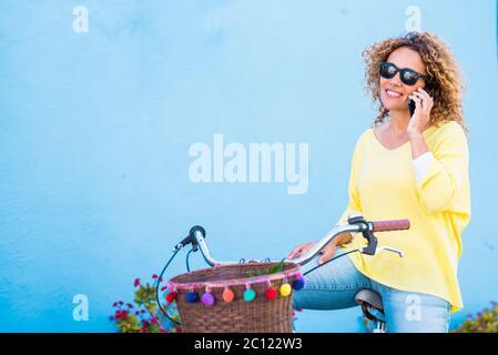 Belle moyenne d'âge bonne santé jeune femme faire un appel téléphonique s'asseoir sur un vélo d'époque coloré heureux et bleu arrière-plan mur - couleurs et les gens heureux