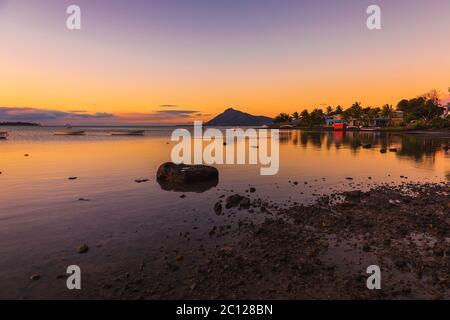 Océan avec bateaux de pêche et ville au coucher du soleil à l'île Maurice. Banque D'Images