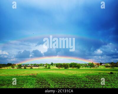 double arc-en-ciel après un orage sur un champ vert.