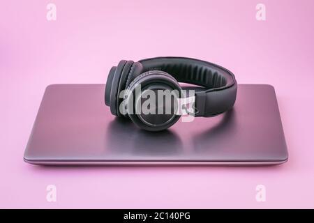 Ordinateur portable et écouteurs fermés. Ordinateur portable métallique et casque portable noir sur fond rose. Concept de divertissement de la réalité virtuelle Banque D'Images
