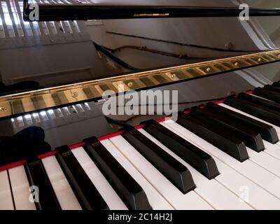 Détail du clavier d'un piano avec touches blanches et noires et couvercle réfléchissant brillant Banque D'Images