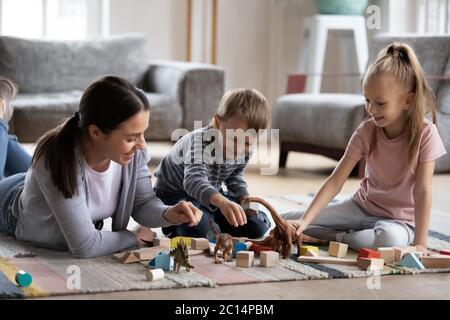 Bonne mère jouant avec une adorable fille et son fils à l'étage Banque D'Images