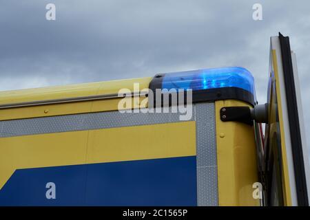 Gros plan d'un véhicule d'urgence avec des feux bleus allumés contre le ciel couvert Banque D'Images