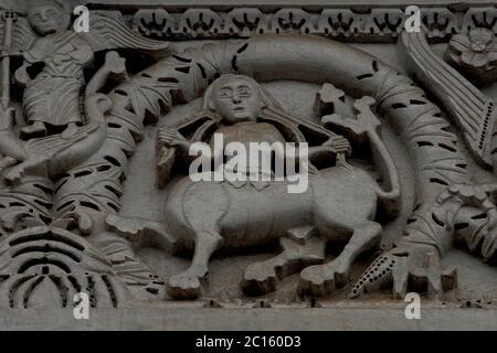 Le symbole chrétien familier de Saint Michael l'Archange tuant un dragon contraste avec des symboles plus proches de l'art pré-chrétien au milieu de la sculpture médiévale exubérante enrichissant la façade ajoutée dans le style roman de Pisan entre le 11ème et le 14ème siècles à la Chiesa di San Michele (église de Saint Michel) Sur la Piazza San Michele, Lucca, Toscane, Italie. Cet exemple, un centaure utilisant ses deux mains humaines pour tirer à ses cheveux longs, est sculpté sur l'architrave du portail central dans le front ouest de l'église. Banque D'Images