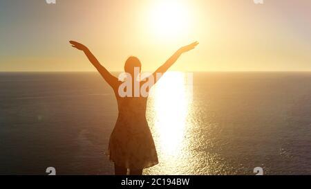 femme en été robe silhouette soulève les mains debout sur le bord de l'océan sans fin face à la lumière du soleil décor arrière vue Banque D'Images