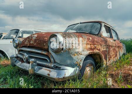 Vieille voiture rétro rouillée abandonnée dans le champ vert. Banque D'Images