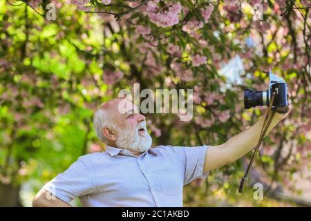temps de selfie. photographe homme prendre la photo sakura de la fleur de gaie. Jardin fleuri de cerisiers. Photographe prenant des photos de célèbres cerisiers en fleurs. Saison de printemps avec fleur rose pleine fleur.