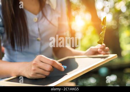 Mains utiliser la craie pour dessiner, écrire le tableau à balckboard dans les parcs. Éducation, concept d'apprentissage. Banque D'Images