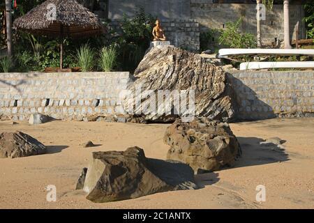 Vue sur la lapa au toit de feuilles de palmier et la statue en bois sur 293 sur Komba Guest House depuis la plage, le village d'Ampangorinana, l'île de Nosy Komba, Madagascar.