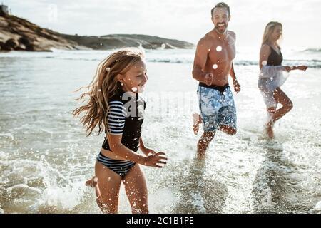 Fille avec ses parents jouant à la plage. Famille de trois personnes qui s'exécutent dans l'eau à la plage.