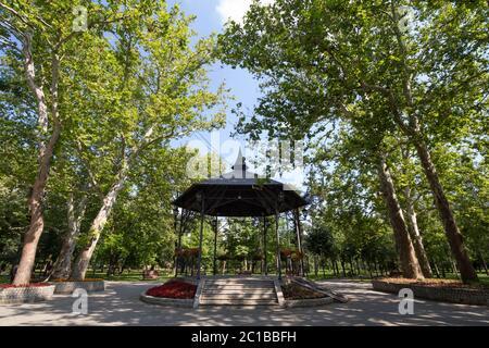 Bandstand dans un parc de la ville en été, entouré de jardins et de grands arbres, avec son stade rond typique et abri en métal. Un kiosque à musique ou un kiosque à musique, Banque D'Images