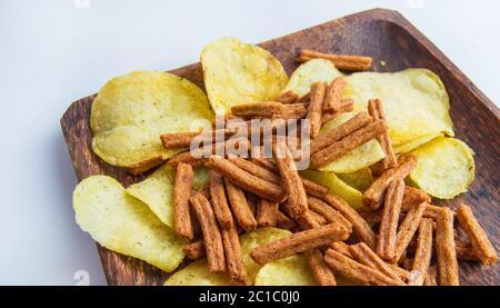 Délicieux croustilles et biscuits salés au pain de seigle sur une assiette en bois sombre, sur fond blanc. En-cas à haute teneur en calories. Banque D'Images