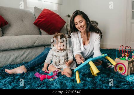 jeune jolie mère joue avec sa fille sur le sol dans le salon à la maison Banque D'Images