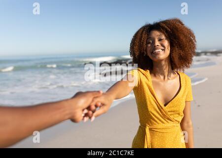 Femme de race mixte souriant sur la plage