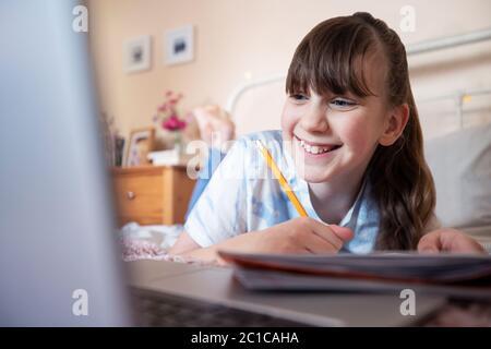Jeune fille couché sur lit dans la chambre avec ordinateur portable étudiant et école à domicile
