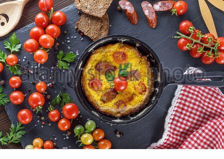 Omelette Poêlée de poulet oeufs avec tomates cerises rouges et fumé de la saucisse dans une poêle rond noir , vue d'en haut Banque D'Images