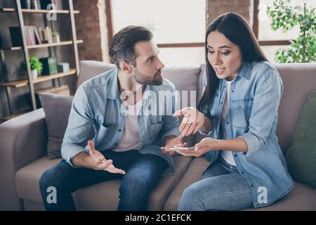 Photo de deux personnes femme utiliser smartphone essayer d'expliquer envie fâchée mari elle n'ont pas un autre homme point main écran se sentir confus assis confort confortable confortable Banque D'Images