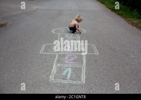 Enfant, blond, jouant au hopscotch dans la rue, l'été