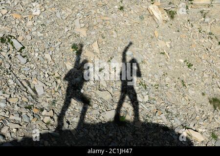 Deux ombres de photographes sur terre qui se dirigent en montant avec des mains surélevées crivent la victoire et le succès. Silhouettes de Banque D'Images