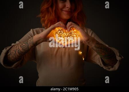 Lumière de Noël en forme de coeur femme tenant dans ses mains autour d'un fond sombre