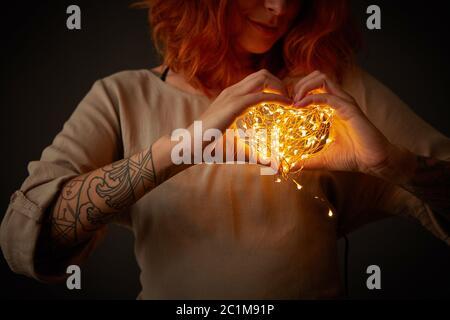Jeune femme avec des guirlandes lumineuses en forme de coeur sur un fond sombre.