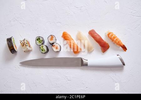 Différents rouleaux de sushi avec les couteaux japonais sur fond ardoise blanc