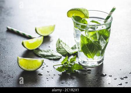 Cocktail avec du citron vert, de la menthe et des glaçons sur une table noire.