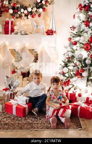 Frère dans deer Christmas hat s'embrasser sa jeune sœur en tête