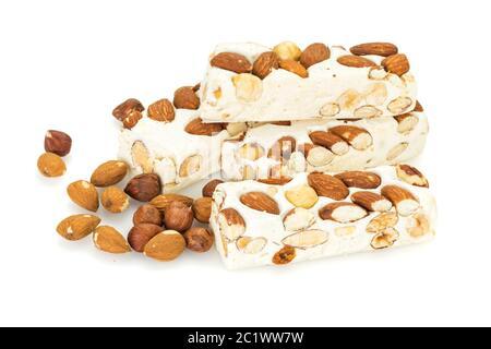 Blocs de Turron disposés avec des amandes et des noisettes , isolés sur fond blanc.