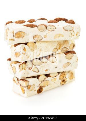 Blocs de turron doux avec amandes et noisettes empilées, isolés sur fond blanc