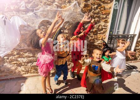 Groupe d'enfants lever les mains en l'air pour atteindre des bonbons portant des costumes d'Halloween debout près du mur avec fantôme dessus Banque D'Images