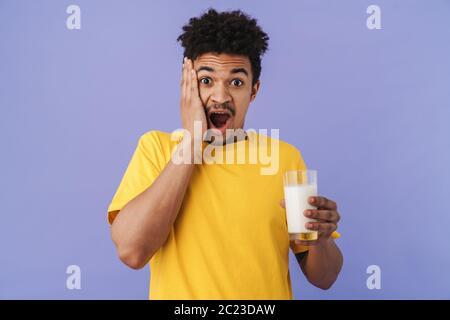 Photo d'un homme afro-américain choqué tenant un verre avec du lait isolé sur fond violet
