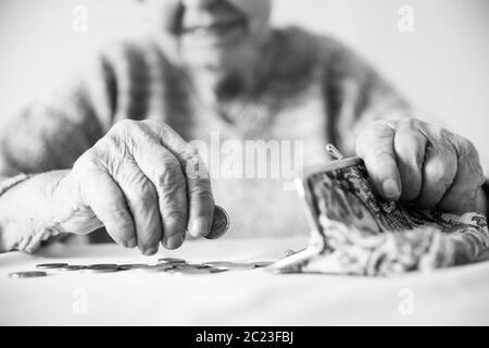 Photo gros plan de personnes âgées 96 ans womans mains restant de comptage de pièces en pension wallet après le paiement des factures. L'insoutenabilité de la tran