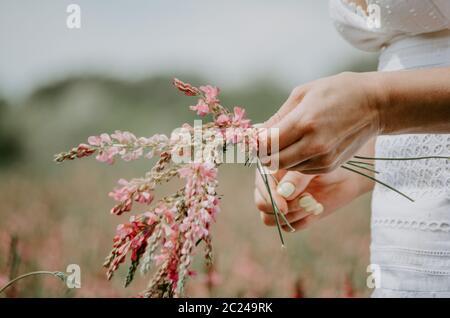 Gros plan sur les mains d'une femme qui tressent des fleurs sauvages dans une couronne de fleurs