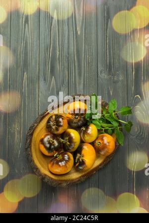 Tomates jaunes tigre de Sibérie sur fond de bois. Récolte de tomates jaunes maison. Tomates jaunes brutes prêtes à manger Banque D'Images