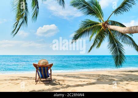 Vue arrière de la jeune belle femme se bronzer et se détendre sur la plage tropicale avec un espace copie