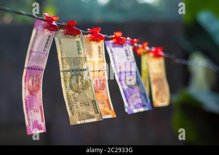 Focus sélectif de nouveaux billets de banque Indiens dix roupies,20,cinquante cent, deux cents, cinq cents et deux mille suspendu dans un fil.