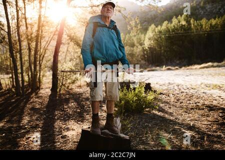 Homme senior en randonnée ne se tenant pas debout et regardant le sommet de la montagne. Homme senior faisant une pause sur le sentier de montagne pour admirer le magnifique natu