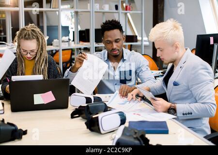 Vie au bureau, travail d'équipe. Trois jeunes gens d'affaires multiethniques, une fille blonde avec des dreadlocks, des hommes africains et caucasiens, assis à la table Banque D'Images
