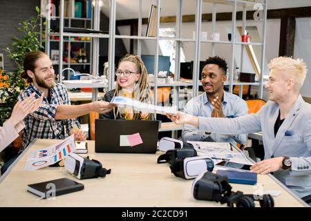 Démarrage, travail d'équipe, brainstorming, concept de réunion. Cinq collaborateurs créatifs travaillant dans des entreprises multiethniques partagent leurs idées tout en planifiant une mise en route conjointe. Deux hommes