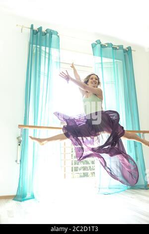 Femme sautant et faisant les fractionnements contre une fenêtre avec rideau avec jupe transparente. Banque D'Images