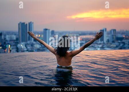 Vue arrière de la femme heureuse liberté avec les bras levés profiter de ses vacances d'été sur la piscine