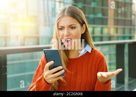 Déçu femme en colère mauvaise réception du contenu en ligne sur téléphone mobile marche dans la rue. Banque D'Images
