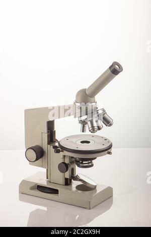 Microscope blanc sur la table sur fond blanc Banque D'Images