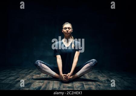 Jeune femme pratiquant le yoga faisant la pose de cobbler sur la pièce sombre