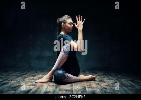 Jeune belle femme faisant yoga asana demi-seigneur des poissons pose sur la pièce sombre Banque D'Images