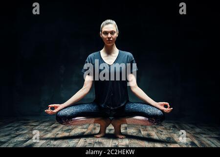 Jeune belle femme faisant yoga asana tiptep pose prapadasana variation sur la pièce sombre Banque D'Images