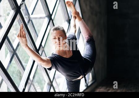 Jeune belle femme faisant yoga asana natarajasana sur fond de grande fenêtre triangulaire Banque D'Images