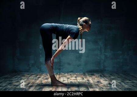 Jeune belle femme faisant yoga asana demi-chaise poser sur la pièce sombre. Banque D'Images